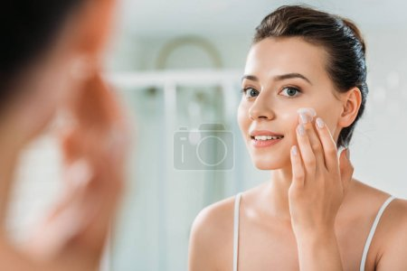 Photo for Selective focus of smiling young woman applying face cream and looking at mirror in bathroom - Royalty Free Image