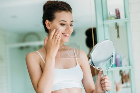 beautiful smiling girl holding mirror and applying facial cream in bathroom