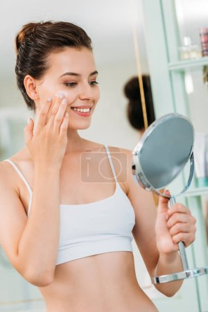 smiling young woman holding mirror and applying facial cream in bathroom