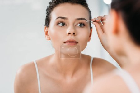 selective focus of girl correcting eyebrows with tweezers and looking at mirror in bathroom