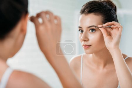 attractive girl correcting eyebrows with tweezers and looking at mirror in bathroom