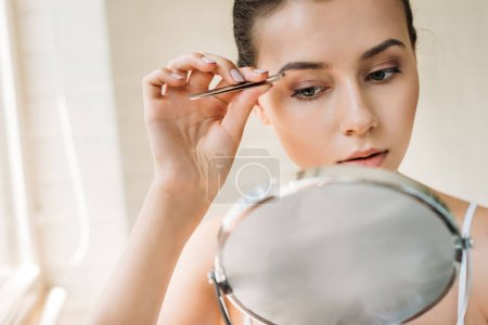 attractive woman correcting eyebrows with tweezers and looking at mirror