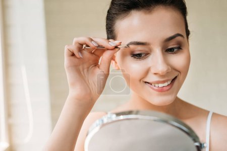 smiling young woman correcting eyebrows with tweezers and looking at mirror