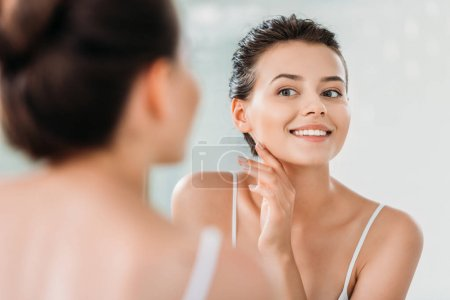 Photo for Beautiful smiling young woman touching skin and looking at mirror in bathroom - Royalty Free Image