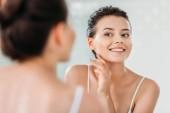 """Постер, картина, фотообои """"красивая молодая женщина, улыбаясь касаясь кожи и глядя в зеркало в ванной комнате"""""""