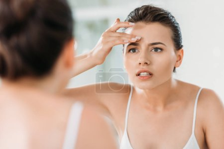 attractive young woman touching forehead and looking at mirror in bathroom