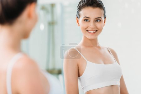selective focus of beautiful smiling girl looking at mirror in bathroom