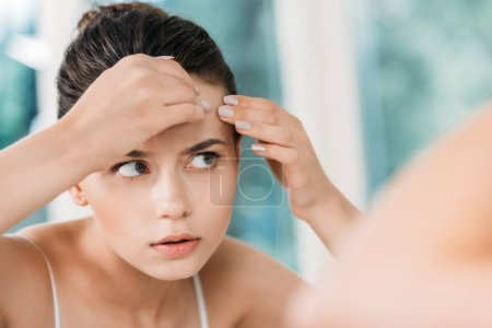 selective focus of girl checking skin on forehead and looking at mirror in bathroom