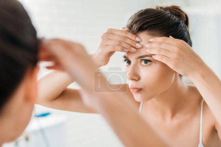 selective focus of young woman checking facial skin and looking at mirror in bathroom