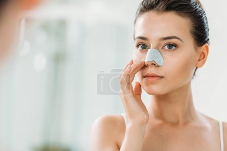 Photo pour Belle fille appliquant bande de nez et regarder miroir sur salle de bain - image libre de droit