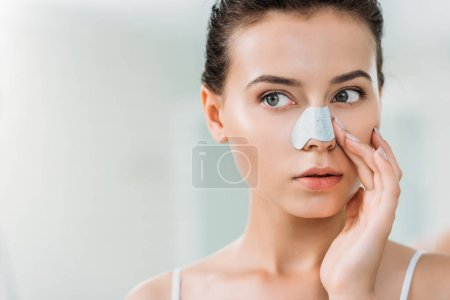 Photo pour Attrayant jeune femme appliquant bande de nez dans la salle de bain - image libre de droit