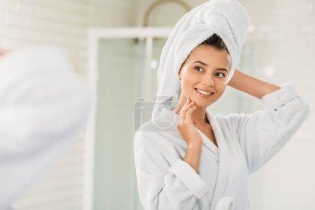 Photo pour Belle jeune femme souriante en peignoir et serviette sur la tête en regardant le miroir dans la salle de bain - image libre de droit