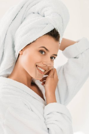 beautiful smiling girl in bathrobe and towel on head in bathroom