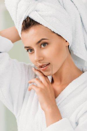 Photo pour Belle fille pensive en peignoir et serviette sur la tête - image libre de droit