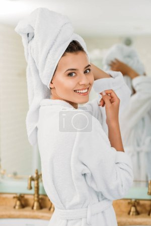 Photo for Attractive young woman in bathrobe and towel on head smiling at camera in bathroom - Royalty Free Image