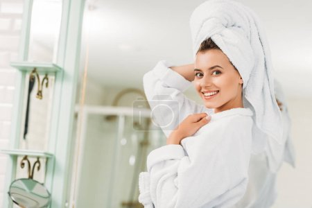 beautiful young woman in bathrobe and towel on head smiling at camera in bathroom