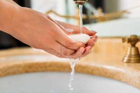 close-up partial view of woman washing hands with soap in bathroom