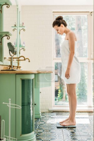Photo for Side view of beautiful young woman in towel standing on digital scales in bathroom - Royalty Free Image