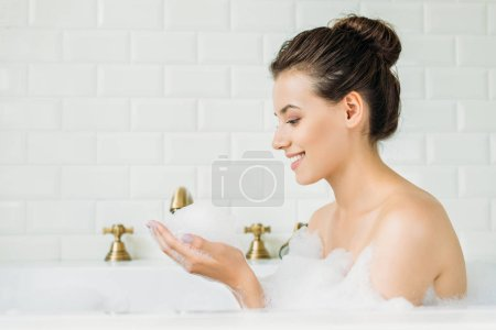 side view of beautiful smiling girl relaxing in bathtub with foam