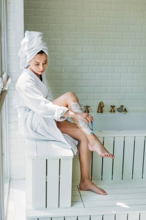 high angle view of beautiful young woman shaving leg with razor in bathroom