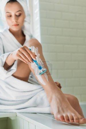 young woman shaving leg with razor in bathroom