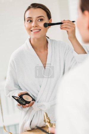 souriante jeune femme en peignoir, miroir en regardant et se maquiller
