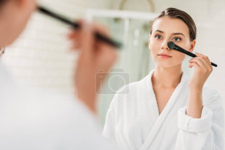 selective focus of beautiful brunette girl in bathrobe looking at mirror and applying makeup