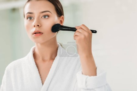 beautiful girl in bathrobe applying bronzer with brush