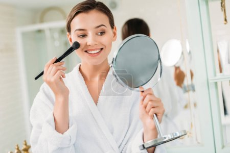 happy young woman in bathrobe holding mirror and applying makeup in bathroom