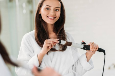 smiling young woman in bathrobe using hair curler in bathroom