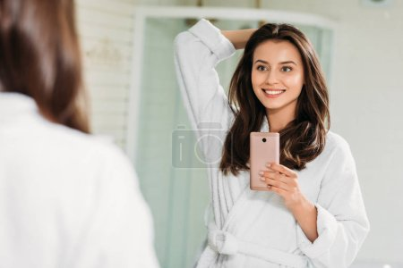 beautiful smiling young woman in bathrobe taking selfie with smartphone in bathroom