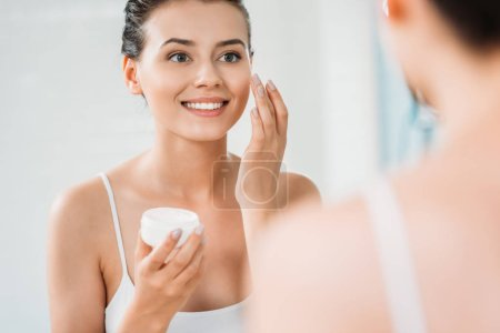 beautiful smiling young woman applying face cream and looking at mirror