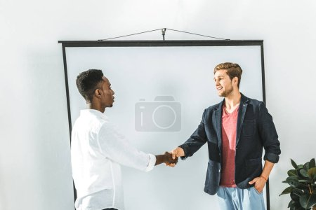 side view of multicultural businessmen shaking hands during business seminar