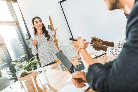 Retrato de joven empresaria asiática que presenta la idea de negocio a colegas durante la reunión