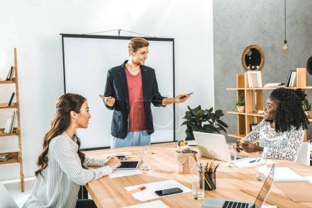 young businessman making presentation for colleagues at meeting in office