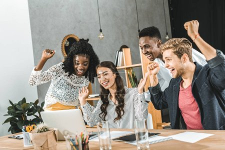 multicultural group of business people celebrating success at workplace with laptop