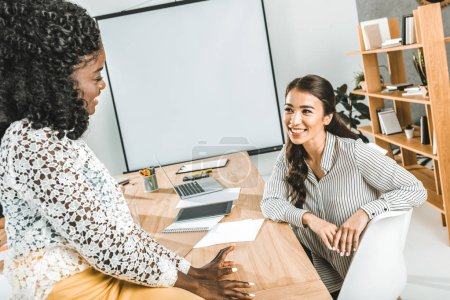 Foto de Mujeres empresarias sonrientes multiétnicas tener conversación en el lugar de trabajo en oficina - Imagen libre de derechos