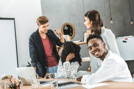Photo pour Homme d'affaires africain-américain, regardant la caméra tandis que collègues avoir discussion sur lieu de travail au bureau - image libre de droit