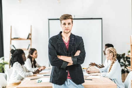 portrait of young businessman with arms crossed standing at table during conference in office