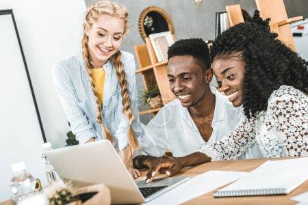 Foto de Empresario sonriente multicultural y empresarias con portátil en el lugar de trabajo en oficina - Imagen libre de derechos