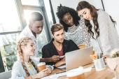 équipe des activités ciblées multiethnique travaillant sur ordinateur portable ensemble au milieu de travail au bureau