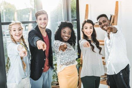 Photo pour Hommes d'affaires souriants multiethniques pointant vers la caméra tout en restant ensemble dans le bureau - image libre de droit