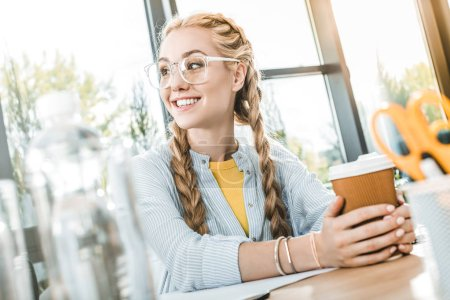 portrait of smiling businesswoman in eyeglasses with coffee to go in hands sitting at table in office