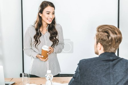 portrait of smiling asian businesswoman with coffee to go talking with colleague in office