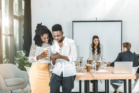 Foto de Sonriendo a empresarios afroamericanos con smartphone juntos en la oficina - Imagen libre de derechos