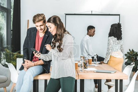 Foto de Gente de negocios multicultural con smartphone mientras que compañeros de trabajo hablar de trabajo en la oficina - Imagen libre de derechos