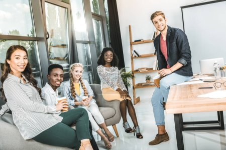 Photo for Multiethnic smiling business coworkers looking at camera while having coffee break in office - Royalty Free Image