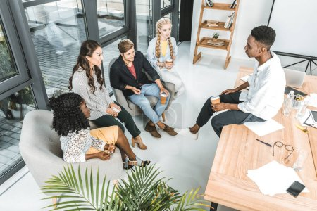 multiethnic group of young business coworkers having coffee break in office