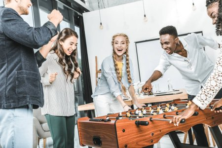multicultural business people celebrating win while playing table football together