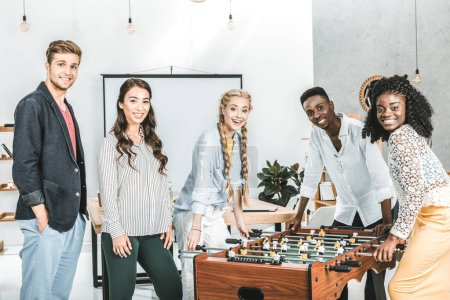 multicultural smiling business people looking at camera while playing table football in office